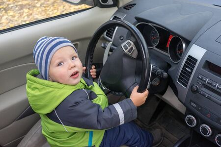 Little boy is sitting at wheel of large car. Imitation of adults, development of independence in children. Imagens