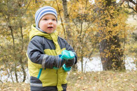 Cheerful little boy with dumbbells during walk in autumn park. Concept of child development, children's sport.