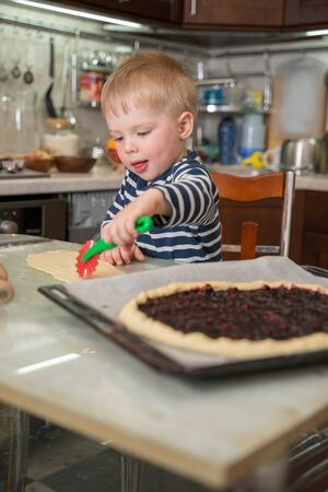 Little cute blond boy in kitchen carefully and curiously cuts dough with children's shaped model knife helping his mother in preparing berry pie. Concept homemade food and little helper.