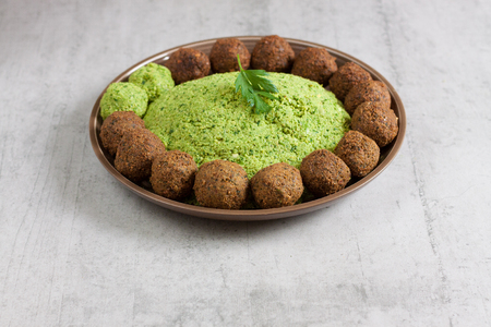 Falafel mixture on a plate arranged with cooked and raw falafel balls.