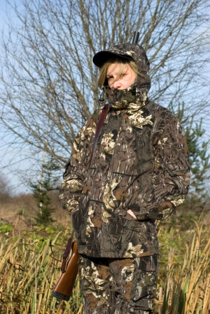 The girl dressed in a camouflage with a gun