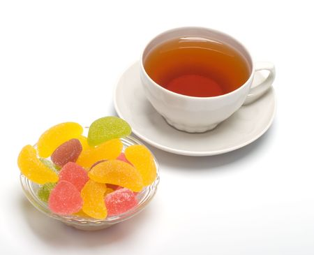 Fruit candy and tea cup. It is isolated on a white background