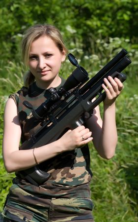 The nice young fair-haired girl with an air rifle. photo