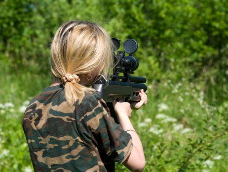 mujer con pistola: El objetivo de una ni�a con una pistola de vista �ptico. Foto de archivo