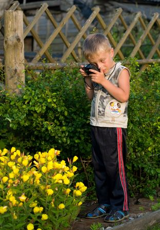 The little boy photographs flowers on a summer residence. Stock Photo - 5227395