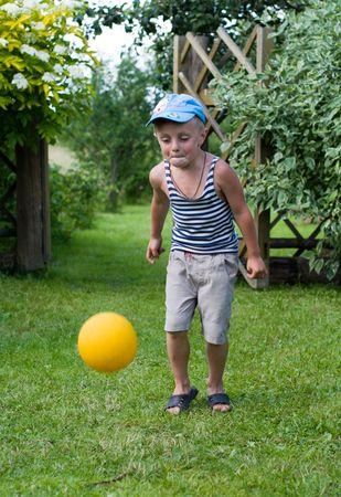 The little boy plays a ball on a grass