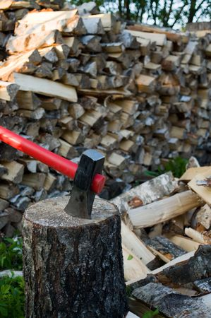 chock: Axe thrust in a birch chock against  woodpile of fire wood. Stock Photo