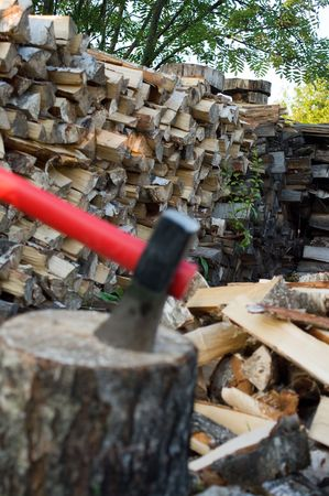 chock: Axe thrust in a birch chock against  woodpile of fire wood. Focus on a woodpile Stock Photo