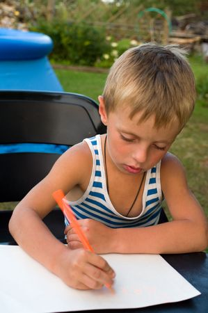The fair-haired boy writes on a sheet of paper a pencil. Stock Photo