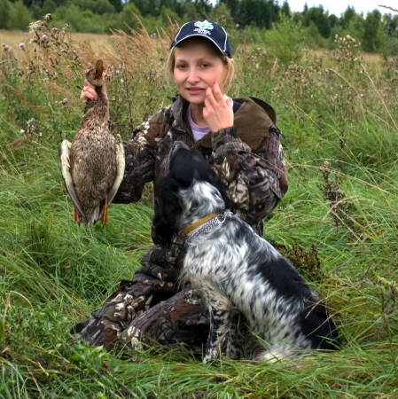 Girl with duck and hunting dog sitting in a field of grass Stock Photo