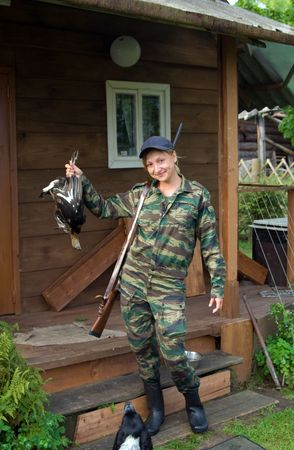 Smiling hunter with a shotgun in his hand grouse.