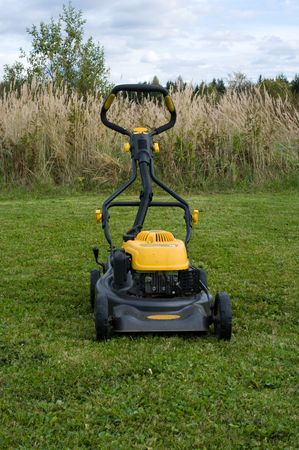 Yellow lawn mower on the green field. Stock Photo