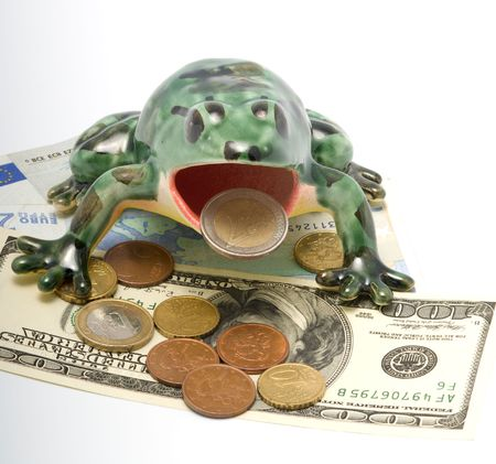 encash: The ceramic frog sitting on money holds in a mouth a coin two euros. Stock Photo