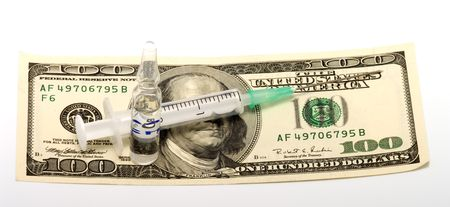 Syringe and ampoule with medicine on  a banknote one hundred dollars. photo