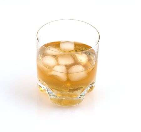 Close up of a glass of whisky with ice cubes on a white glossy background. Stock Photo