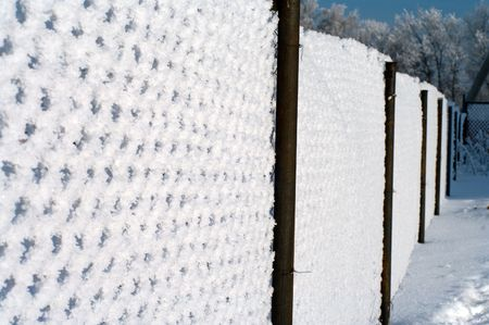 Metal wire mesh fence covered with snow. photo
