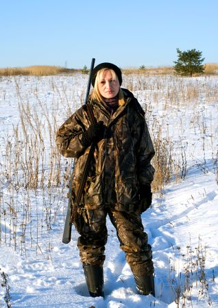 camouflage woman: The female hunter on a winter field with a shot-gun.