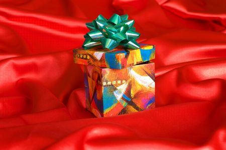 Gift box on a red satin cloth. photo