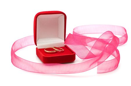 Wedding rings in the red box and a pink ribbon on a white background. Stock Photo - 6524650