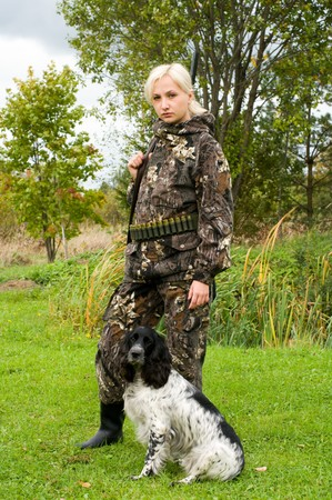 Blonde in camouflage with a gun and hunting dog. photo