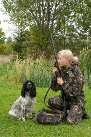 Blonde in camouflage with a gun and russian hunting spaniel. photo