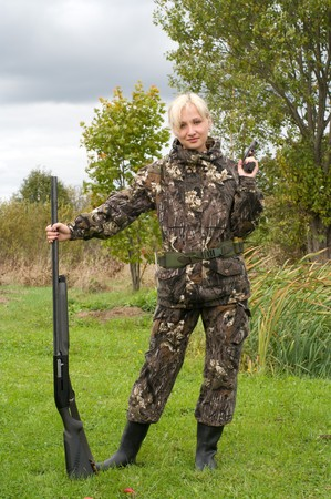 Blonde in camouflage with a shotgun and a pistol.
