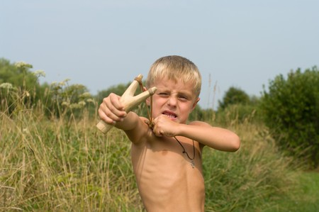 The boy aims from a wooden slingshot in the afternoon. photo