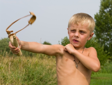 The boy shoots from a wooden slingshot in the afternoon. photo
