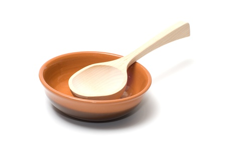 Wooden spoon in a brown ceramic plate.