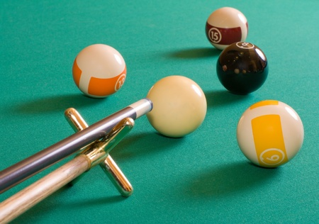 Cue and pool balls on a billiard table. Stock Photo