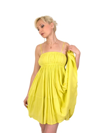 Blonde in yellow summer dress looks down thoughtfully.