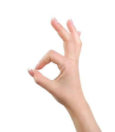 Womans hand close-up shows a gesture ok is isolated on a white background.