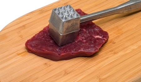 Piece of beef and a kitchen mallet on a wooden cutting board. photo