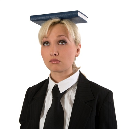Blonde girl holds the book on a head is isolated on a white background.  photo