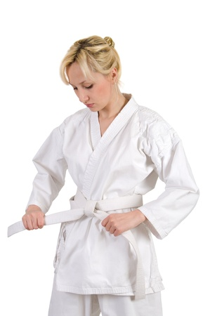 Blonde girl ties the belt on a kimono is isolated on a white background. Stok Fotoğraf