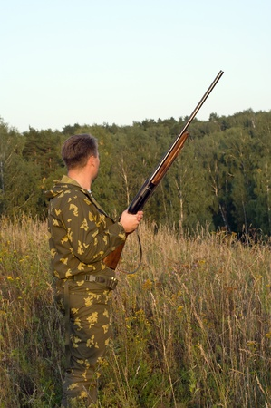 Outdoor shoot of man in camouflage with a shotgun. photo