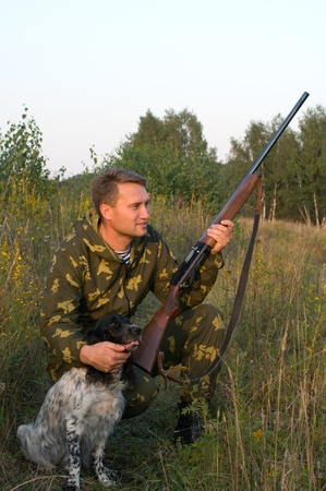 Man in camouflage with a gun and russian hunting spaniel. Stok Fotoğraf