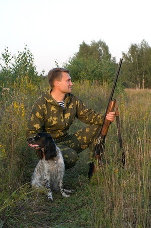 hunting rifle: Man in camouflage with a gun and russian hunting spaniel. Stock Photo