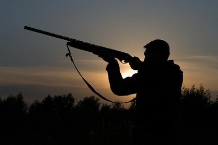 охотник: Силуэт охотника с ружьем на фоне вечернего неба.