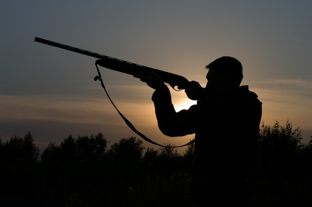 Silhouette of the hunter with a gun against the evening sky. Stock Photo