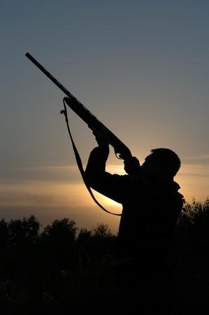 fusil de chasse: Silhouette du chasseur avec une arme contre le ciel de la soir�e.