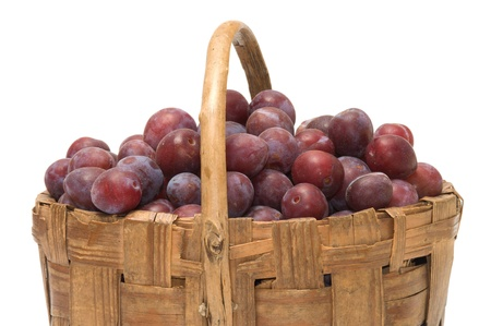 Wattled basket with ripe plums it is isolated on a white background. Stock Photo - 10443596