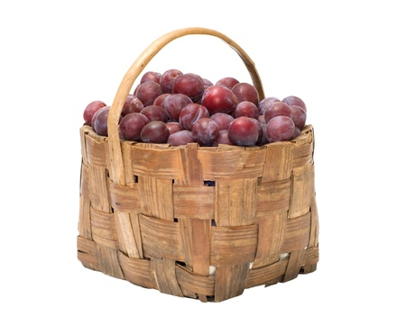 Wattled basket with ripe plums it is isolated on a white background. Stock Photo - 10574059