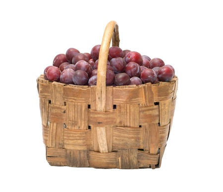 Wattled basket with ripe plums it is isolated on a white background. Stock Photo - 10574063