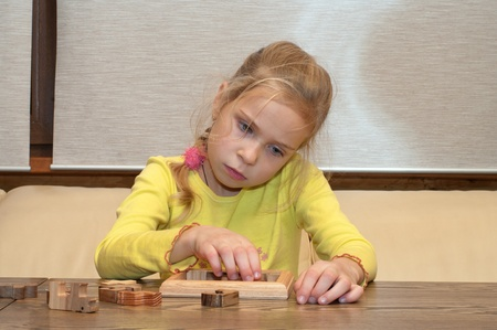 Thoughtful blonde girl collects a puzzle. photo