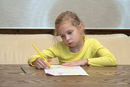 girl drawing: Portrait of the thoughtful lovely girl drawing color pencils. Stock Photo