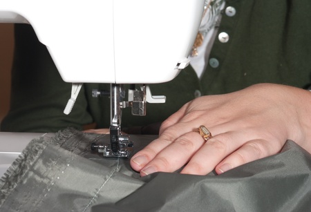 making dresses: Female hands sewing on a machine. Stock Photo