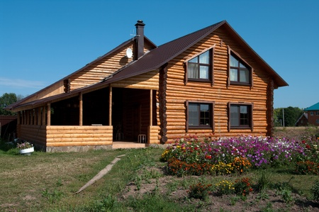 Country log house in the sunny summer day.