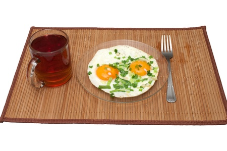 Fried eggs with green onions and a cup of tea on a bamboo mat.