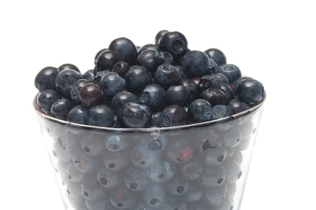 Glass filled by a bilberry it is isolated on a white background.